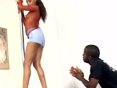 America in fishnet top dancing near the pole